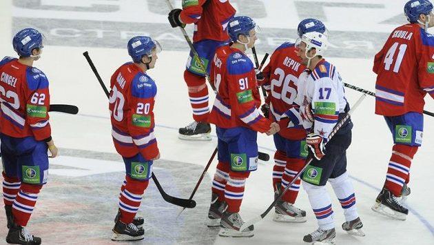 Hokejisté Lva Praha (v červených dresech) se zdraví s útočníkem Petrohradu Iljou Kovalčukem