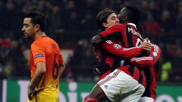 Sulley Muntari (vpravo) se raduje se svými spoluhráči z AC Milán z gólu. Vpravo smutný Xavi z Barcelony.