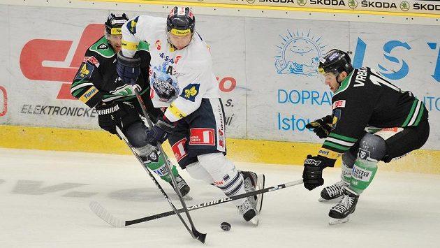Zleva útočník Boleslavi Lukáš Pabiška, útočník Liberce Martin Bartek a útočník David Vrbata bojují o puk.