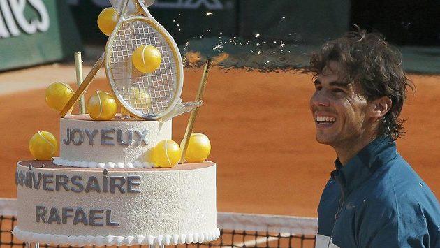 Rafael Nadal si prohlíží narozeninový dort, který dostal od pořadatelů Roland Garros.