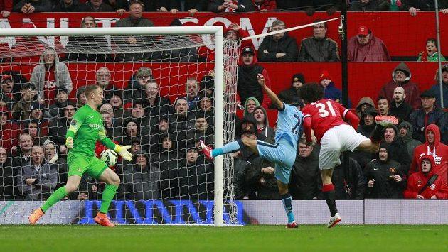 Marouane Fellaini z Manchesteru United (vlevo) střílí gól do sítě Manchesteru City.