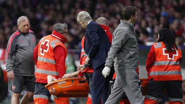 Laurent Koscielny z Arsenalu po zranění opouští hrací plochu na nosítkách.
