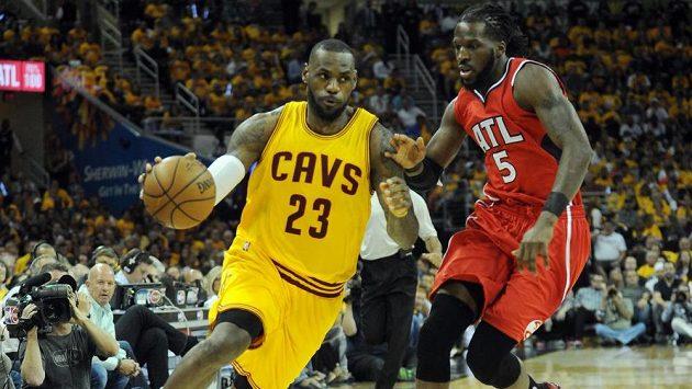 Basketbalista Clevelandu LeBron James (vlevo) si kryje míč před Carrollem z Atlanty.