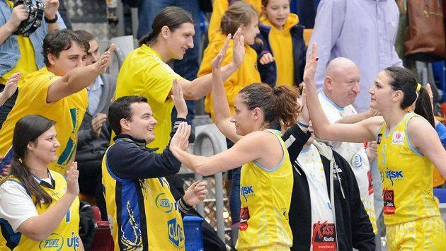 Zprava vpředu Sonja Petrovičová a Laia Palauová z USK Praha slaví s fanoušky výhru nad francouzským Montpellier.