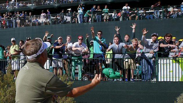 Golfista Ken Duke se chystá do početného publika hodit své tričko.