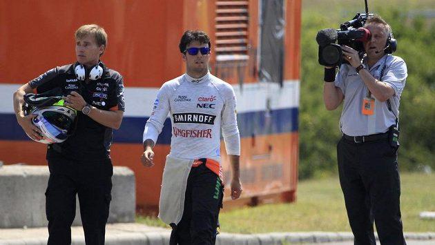 Sergio Pérez (uprostřed) z Mexika míří po tréninkové nehodě nezraněn do depa.