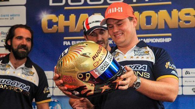 Adam Lacko si zálibně prohlíží zlatou přilbu, kterou od svého týmu Buggyra dostal za titul mistra Evropy. Zleva přihlíží manažer Jan Kalivoda a parťák David Vršecký.