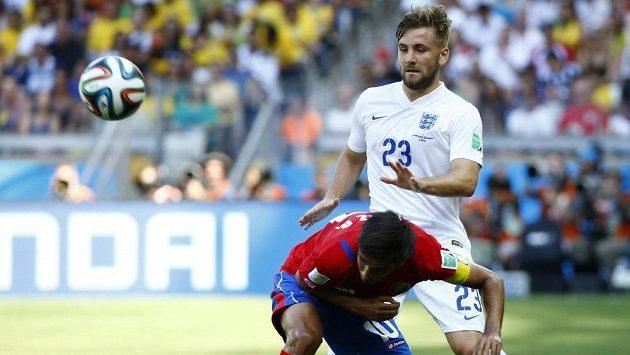 Luke Shaw (č. 23) v dresu Anglie bojuje na MS v Brazílii o míč s Bryanem Ruizem z Kostariky.