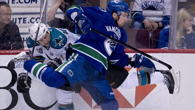 Obránce Dan Hamhuis z Vancouveru v souboji s Andrewem Desjardinsem (10) ze San Jose.