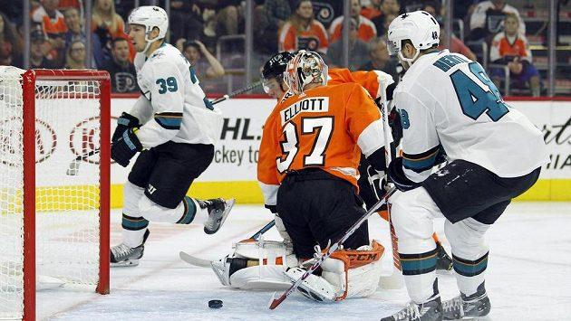 Puk už míří ven z branky Philadelphie, vlevo autor gólu San Jose Logan Couture (39), vpravo Tomáš Hertl, mezi nimi brankář Flyers Brian Elliott.