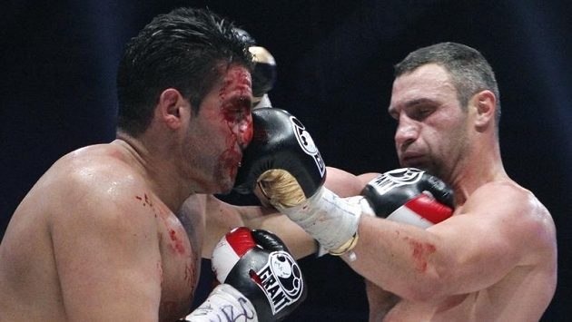 Vitalij Kličko (vpravo) zasazuje úder zkrvavenému Manuelu Charrovi.
