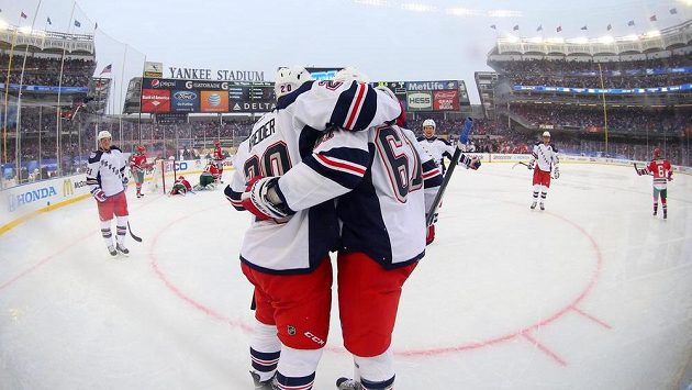 Hokejisté NY Rangers oslavují vstřelený gól v síti New Jersey při utkání pod širým nebem na stadiónu baseballistů Yankees.