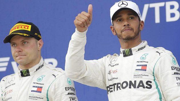 Kontrastní rozpoložení jezdců Mercedesu. Zatímco Lewis Hamilton (vpravo) rozdává úsměvy, Valtterri Bottas vypadá zaraženě.