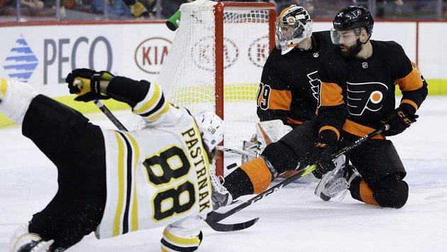 David Pastrňák střílí v akrobatické pozici první gól Bostonu v utkání proti Philadelphii. Brankář Carter Hart ani obránce Radko Gudas už zasáhnout nestačili.