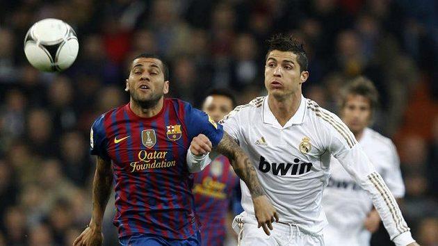 Daniel Alves z Barcelony (vlevo) v souboji s Cristianem Ronaldem