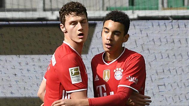 Jamal Musiala (vpravo) a Benjamin Pavard z Bayernu se radují z gólu proti Wolfsburgu.