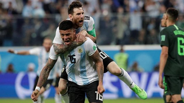 Argentinec Marcos Rojo slaví druhý gól proti Nigérii, na zádech má Lionela Messiho.