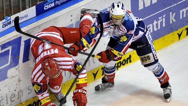 Momentka ze třetího utkání čtvrtfinále play off hokejové extraligy mezi Pardubicemi a Třincem - zleva Jan Peterek z Třince a Václav Benák z Pardubic.