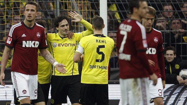 Stoper Dortmundu Mats Hummels (druhý zleva) a jeho spoluhráč Sebastian Kehl slaví gól v duelu s Norimberkem. Zcela vlevo je český útočník Tomáš Pekhart.