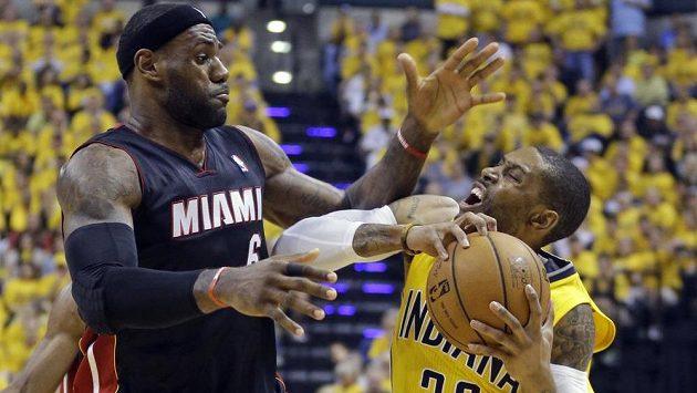 Hvězdný LeBron James (vlevo) z Miami v souboji se C.J. Watsonem z Indiany.