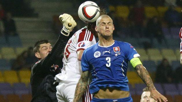 Slovenský brankář Matúš Kozáčik zasahuje v kvalifikačním duelu v Bělorusku. Vpravo je obránce Martin Škrtel.