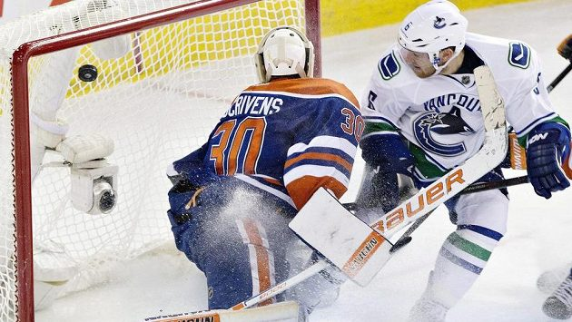 Hokejista Vancouveuru Canucks Yannick Weber (vpravo) dává gól brankáři Edmontonu Oilers Benu Scrivensovi.