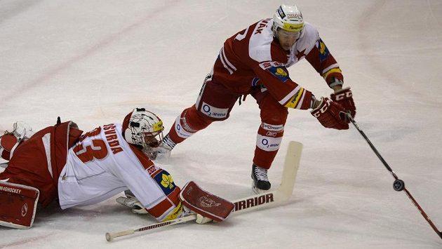 Hokejista Slavie Jan Novák (vpravo) se snaží překonat olomouckého gólmana Tomáše Vošvrdu v 10. kole baráže.