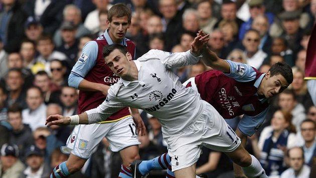 Záložník Tottenhamu Gareth Bale padá na zem po souboji s obráncem Aston Villy Matthew Lowtonem.