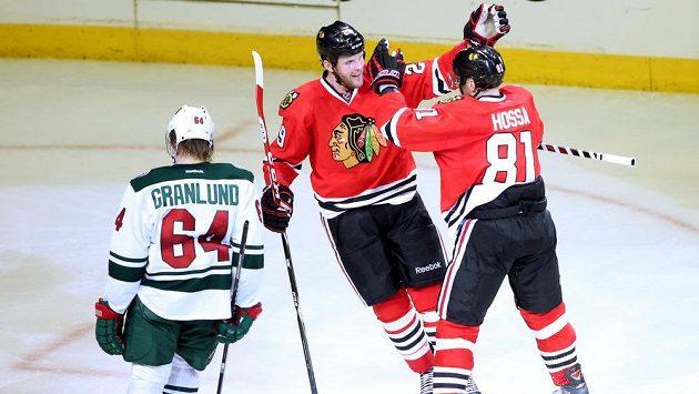 Hráči Chicaga Blackhawks Bryan Bickell (uprostřed) a Marián Hossa (81) slaví druhou výhru v play off NHL nad Minnesotou.
