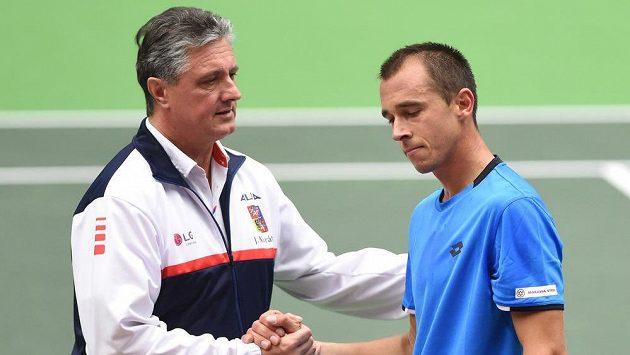 Nehrající daviscupový kapitán Jaroslav Navrátil si podává ruku s Lukášem Rosolem po porážce s Bernardem Tomicem.