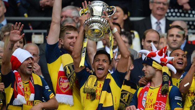 Útočník Arsenalu Alexis Sánchez (uprostřed) s trofejí pro vítěze anglického FA Cupu.