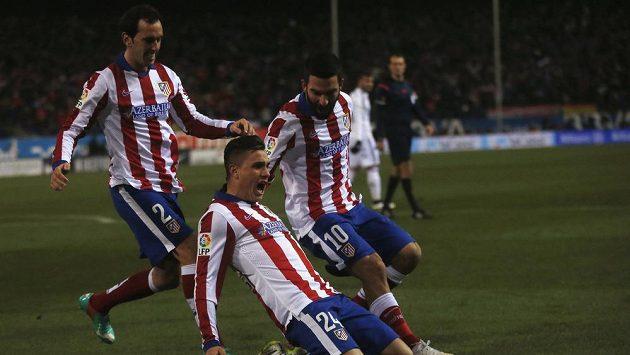Stoper Atlétika Madrid José María Giménez de Vargas (uprostřed) slaví se spoluhráči Diegem Godínem (vlevo) a Ardou Turanem gól proti Realu.