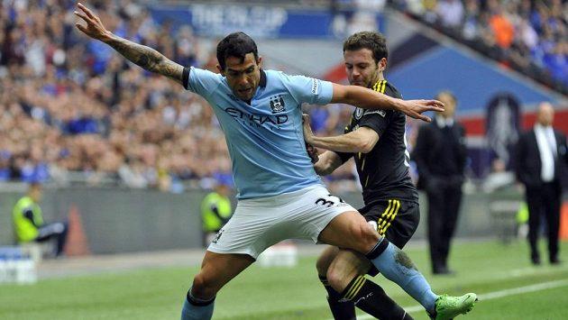 Carlos Tévez z Manchesteru City (vlevo) si kryje míč před Juanem Matou z Chelsea.