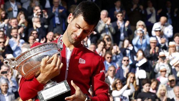 Srbský tenista Novak Djokovič si prohlíží trofej pro vítěze French Open.
