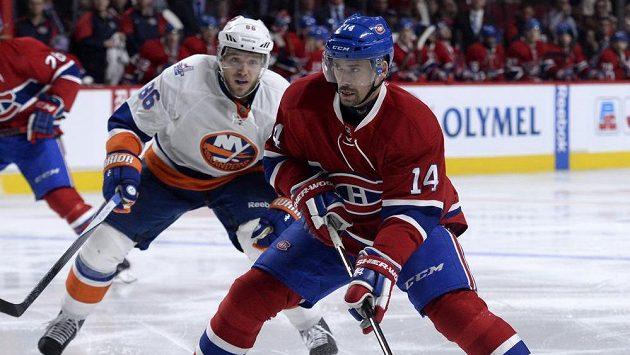 Hokejista Montrealu Tomáš Plekanec (vpravo) se připravuje ke střele v utkání proti New Yorku Islanders. Hosující Nikolaj Kuljomin jen přihlíží.