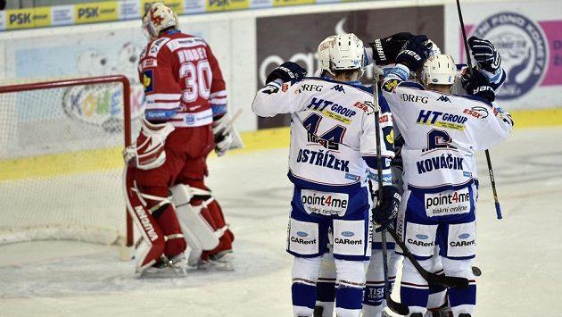 Hokejisté Komety slaví gól v síti Třince. Vlevo je zklamaný brankář Ocelářů Šimon Hrubec.