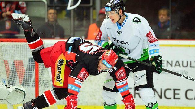 Hokejista Rudolf Červený z Hradce v akrobatické pozici po souboji s Davidem Němečkem z Mladé Boleslavi během utkání 35. kola extraligy.