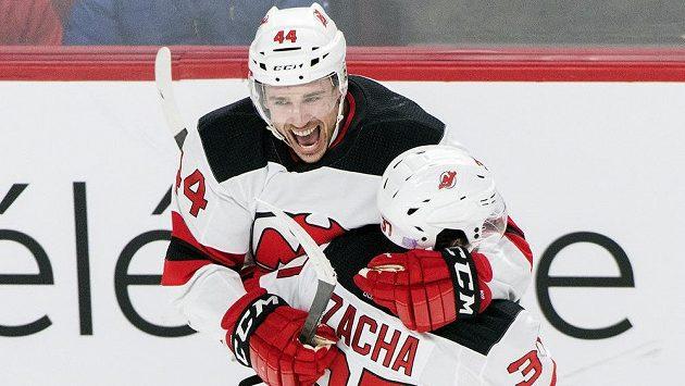 Hokejisté New Jersey Devils Miles Wood (44) a Pavel Zacha oslavují gól proti Montrealu.