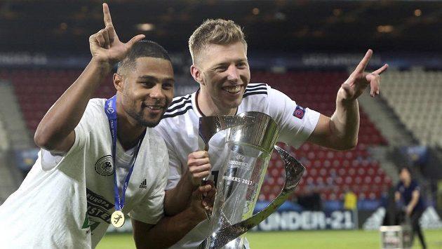 Německý fotbalista Serge Gnabry (vlevo) pózuje společně se spoluhráčem Mitchellem Weiserem s vítěznou trofejí pro evropské šampióny do 21 let.