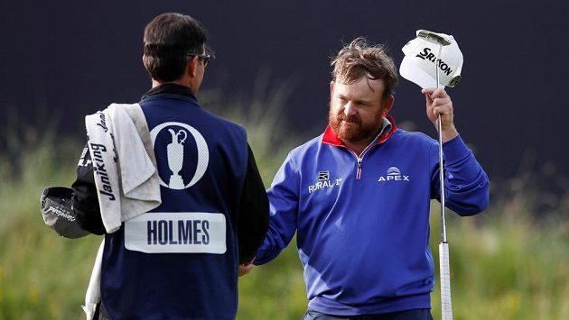 Americký golfista J.B. Holmes a jeho caddie pop rvním kole.