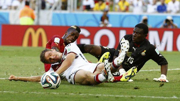 Thomas Müller z Německa (vpředu) bojuje o míč s ghanskou defenzívou v čele s gólmanem Daudou.
