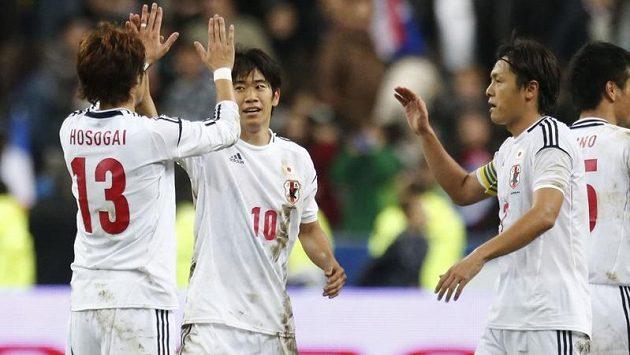 Japonští fotbalisté se radují z výhry nad Francií.