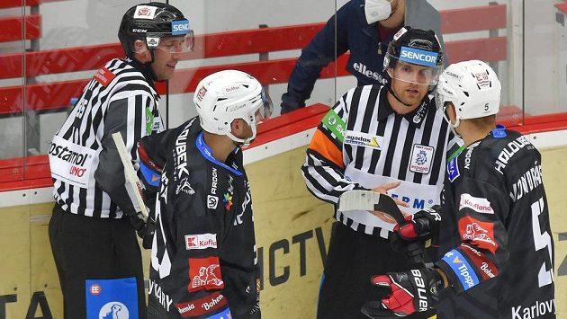 Petr Koblasa (vlevo) a kapitán Tomáš Vondráček z Karlových Varů se dohadují s rozhodčími těsně před koncem utkání o osobním trestu pro Koblasu.