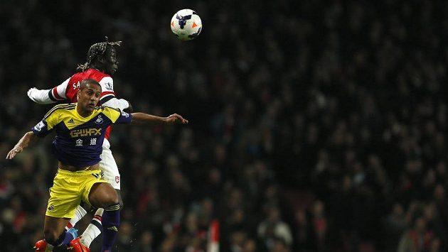 Pravý obránce Arsenalu Sagna vítězí v hlavičkovém souboji proti Routledgeovi ze Swansea (v popředí).