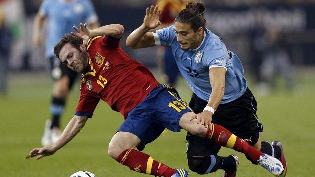 Uruguayec Martin Caceres (vpravo) bojuje o míč se Španělem Juanem Matou v přátelském zápase.