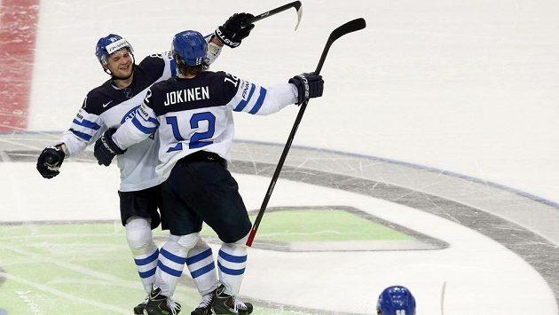 Finský útočník Iiro Pakarinen (vlevo) slaví se spoluhráčem Jokinenem (R) výhru nad Švýcarskem.