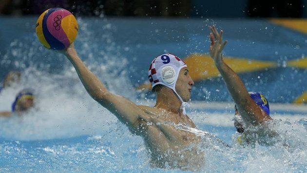Chorvatský vodní pólista Sandro Sukno (vlevo) napřahuje ke střele na branku Černé Hory v semifinále olympijských her v Londýně.