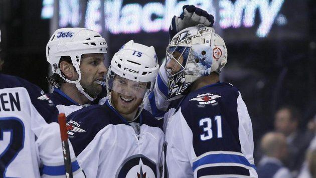 Obránce Winnipegu Mark Stuart (vlevo), útočník Matt Halischuk a gólman Ondřej Pavelec slaví výhru nad Torontem.