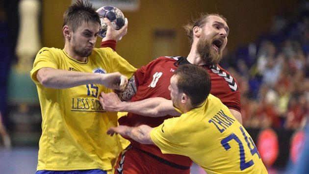 Český házenkář Pavel Horák se snaží zakončit akci tvrdě bráněný Ukrajinci Oleksandrem Tiltem a Jevgenem Žukem v kvalifikačním utkání mistrovství Evropy 2018.