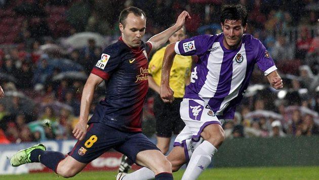 Barcelonský Andreas Iniesta se napřahuje ke střele. Vpravo Marc Valiente z Realu Valladolid.